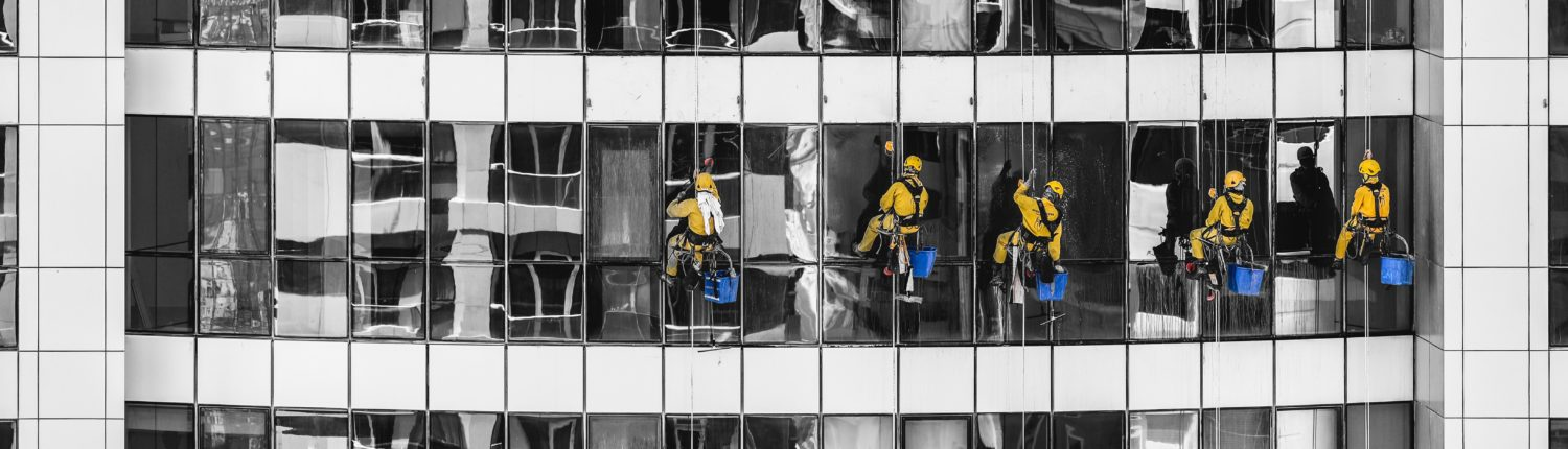 Workers cleaning windows of a high rise building